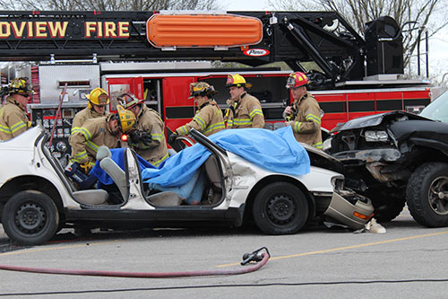 Members of the Grandview Fire Department work the scene of a staged traffic accident at Grandview High School. The mock crash was designed to remind students of the dangers of distracted driving.