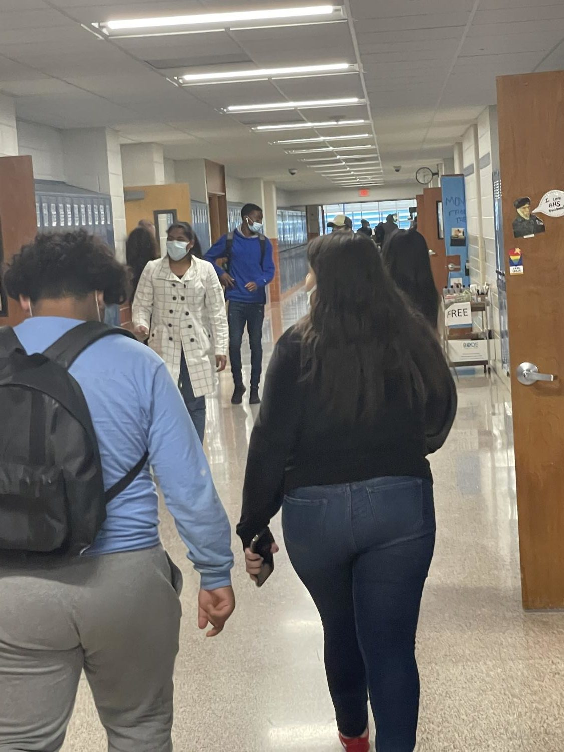 Students walking in the halls while keeping their masks up and over their noses.